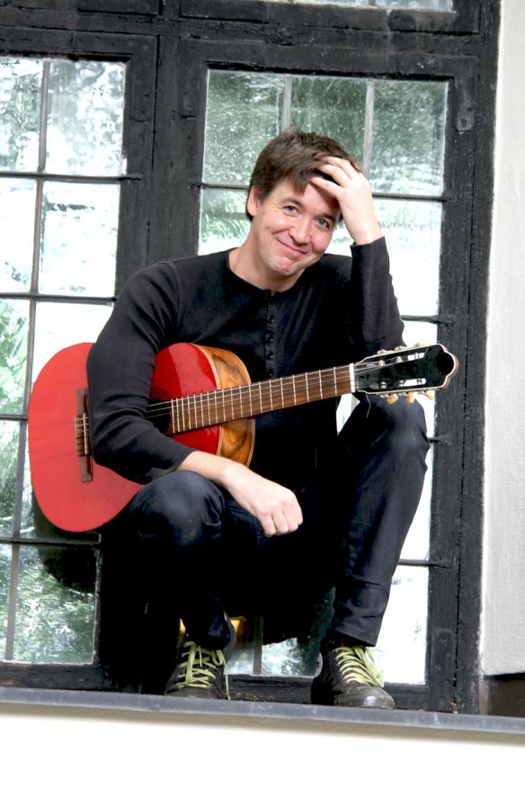 Stefan Jämtbäck med gitarr i fönstret